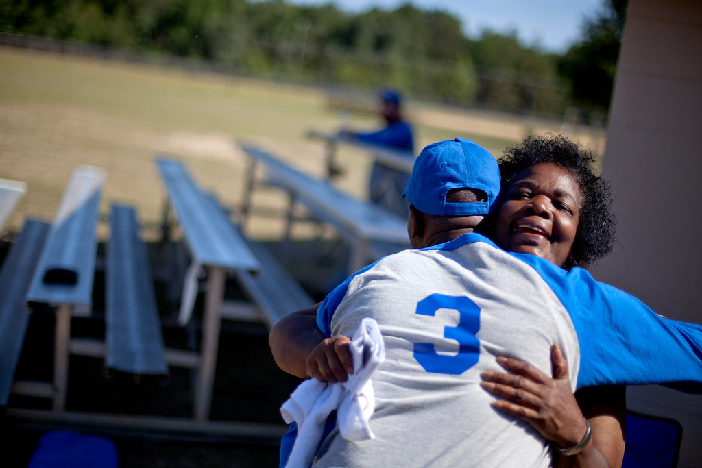 """. Shirley Ann Jordan, right, hugs her son Jimmie Burnette, left, after watching him play blind baseball for the first time since he lost his vision to a brain tumor in 2010, in Albany, Ga. on May 5, 2012. \""""That\'s the first time son. There\'s a first time for everything. You did good. Excellent! I\'m proud of you. Very proud.\"""" (AP Photo/David Goldman)"""