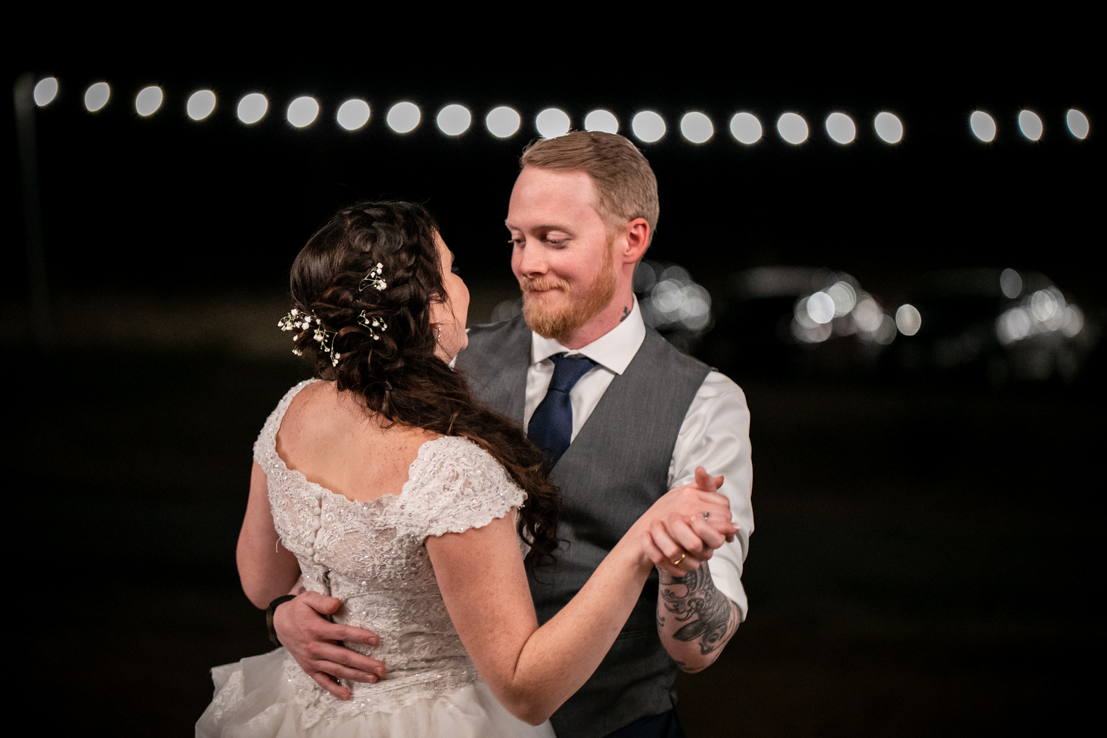 bride and groom dance outside away from the guests on their wedding night