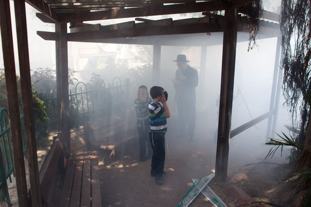 . Children cover their faces from smoke as leavened items are  burned in a final preparation before the start at sundown of the Jewish Pesach (Passover) holiday on March 25, 2013 in Bnei Brak, Israel. Religious Jews throughout the world eat matzoth during the eight-day Passover, or Pesach, holiday, The Jewish holiday commemorates the Israelis\' exodus from Egypt some 3,500 years ago and their ancestors\' plight by refraining from eating leavened food. Passover begins March 25 and ends on the evening of April 02.  (Photo by Uriel Sinai/Getty Images)