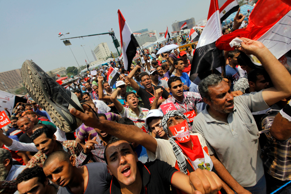 ". Opponents of Egypt\'s Islamist President Mohammed Morsi shout slogans during a protest in Tahrir Square in Cairo, Egypt, Wednesday, July 3, 2013. A Defense Ministry official said army chief Gen. Abdel-Fattah el-Sissi is meeting with his top commanders, hours before the military\'s deadline to the president and opposition to resolve the nation\'s political crisis is set to expire. Arabic reads, ""Leave.\"" (AP Photo/Amr Nabil)"