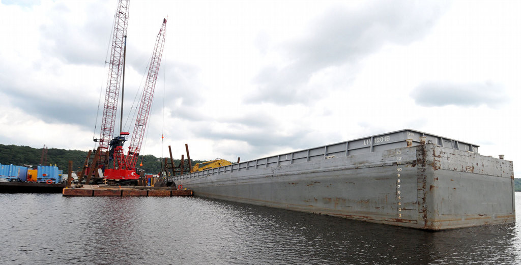 . The work platform, left, fills the barge, right, with material, mostly muck and sand, from the St. Croix River bottom as initial work progresses on the footings of the new bridge Monday. To put up the new St. Croix River bridge, crews must dredge up more than 2,500 dump trucks� worth of muck, sand and gravel from the river bottom. (Pioneer Press: John Doman)
