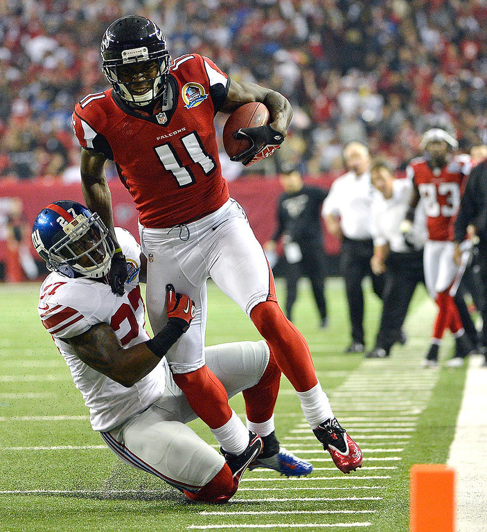 . Atlanta Falcons wide receiver Julio Jones (11) runs as Atlanta Falcons cornerback Robert McClain (27) makes the tackle during the second half of an NFL football game on Sunday, Dec. 16, 2012, in Atlanta. (AP Photo/Rich Addicks)