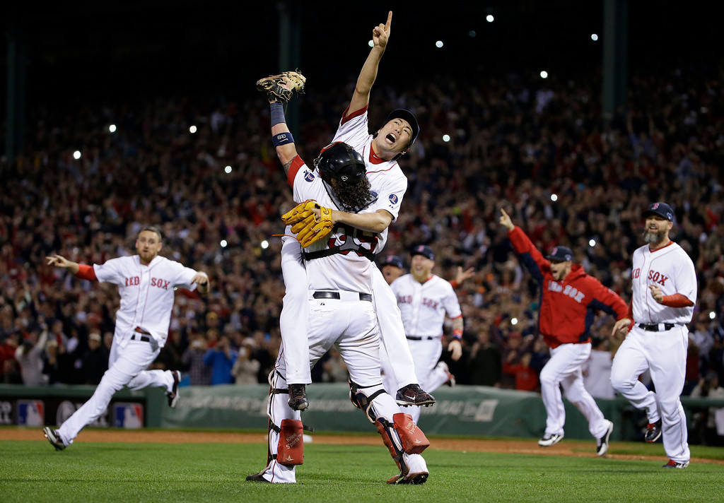 . Boston Red Sox relief pitcher Koji Uehara, rear, and catcher Jarrod Saltalamacchia celebrate the Red Sox 5-2 win over the Detroit Tigers in Game 6 of the American League baseball championship series on Saturday, Oct. 19, 2013, in Boston. The Red Sox advance to the World Series. (AP Photo/Matt Slocum, File)