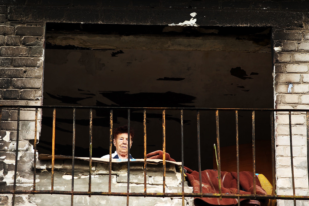 . ALOVAISK, UKRAINE - SEPTEMBER 10: A woman looks out from the balcony of her building which was damaged during heavy fighting in August on September 10, 2014 in Alovaisk, Ukraine.(Photo by Spencer Platt/Getty Images)