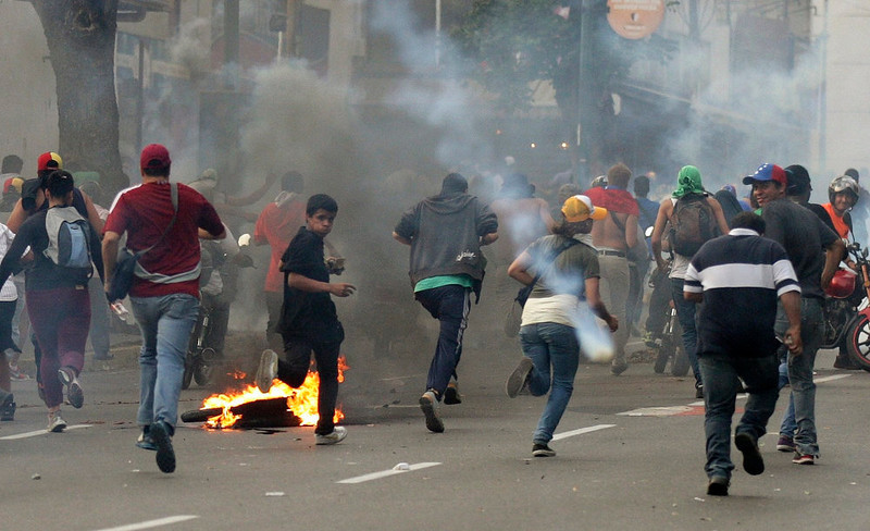 . Supporters of opposition leader Henrique Capriles run away from tear gas fired by riot police as they demonstrated for a recount of the votes in Sunday\'s election, in Caracas, April 15, 2013. Hundreds of protesters clashed with police in the Venezuelan capital on Monday after Capriles called for demonstrations to demand a recount of votes from Sunday\'s election to replace the late Hugo Chavez.  REUTERS/Christian Veron
