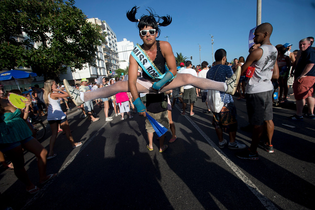 ". A reveller performs a split jump at the Simpatia e Quase Amor or ""Kindness is almost love,\"" block party, a pre-Carnival celebrations in Rio de Janeiro, Brazil, Saturday, Feb. 2, 2013. According to Rio\'s tourism office, Rio\'s street Carnival this year will consist of 492 block parties, attended by an estimated five million Carnival enthusiasts. (AP Photo/Silvia Izquierdo)"