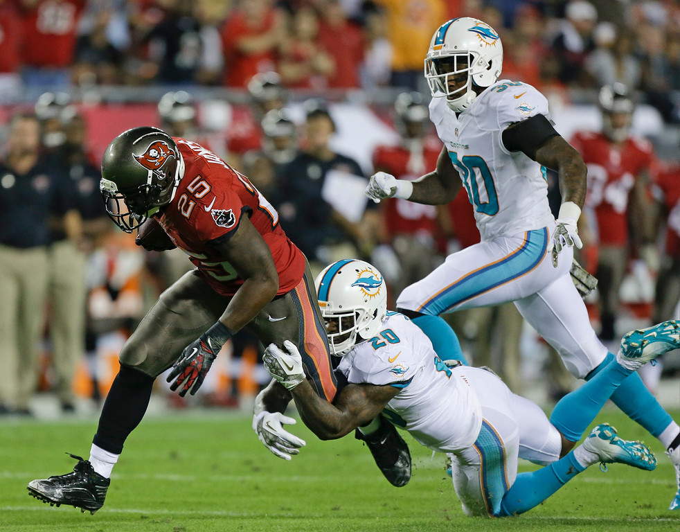 . Tampa Bay Buccaneers running back Mike James is tackled by Miami Dolphins free safety Reshad Jones (20) after gaining 24-yards during the first half of an NFL football game in Tampa, Fla., Monday, Nov. 11, 2013.(AP Photo/John Raoux)