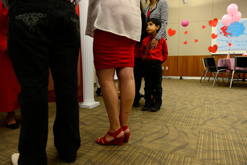 . DENVER, CO - FEBRUARY 14: Joel Herrera watches as his parents Joel Herrera and Sylvenvestra Rodriguez get married during a Valentine\'s Day celebration at the Denver Clerk and Recorder\'s office. Couples applying for marriage licenses received gift bags containing gift certificates to local restaurants among other treats to celebrate their union. (Photo By AAron Ontiveroz/The Denver Post)