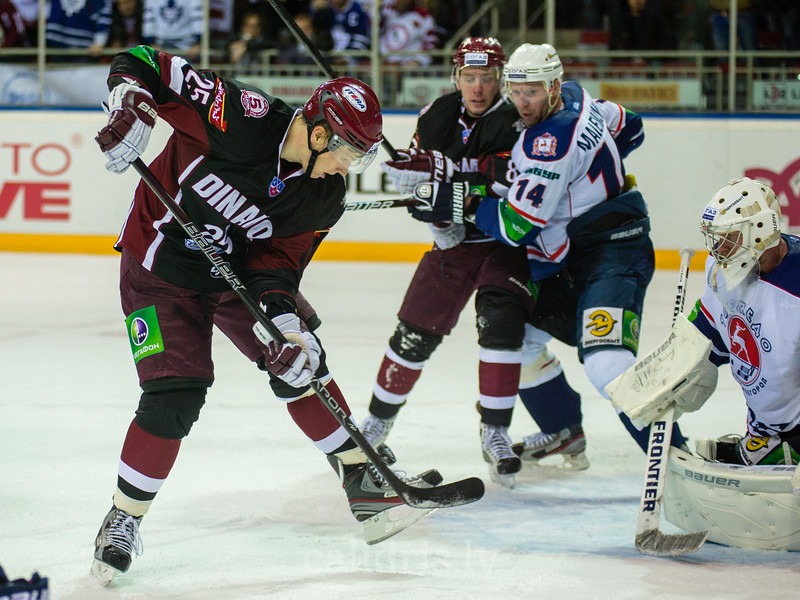 Andris Dzerins (25) kicks the puck in front of the goal