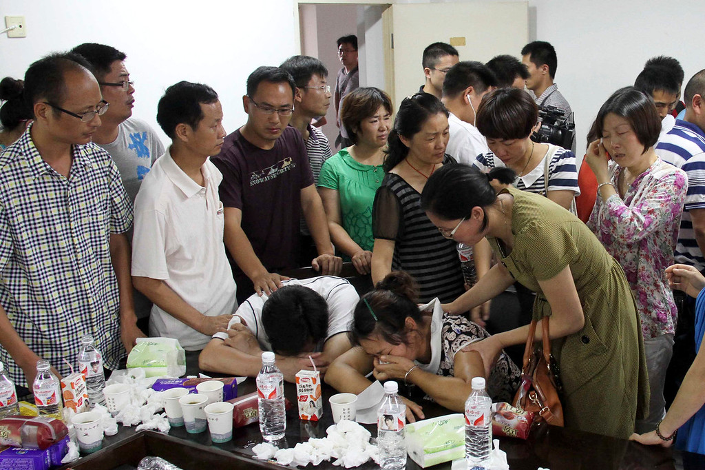 . Parents of Wang Linjia, center, are comforted by parents of some other students who were on the Asiana Airlines Flight 214 that crashed at San Francisco International Airport, at Jiangshan Middle School in Jiangshan city, in eastern China\'s Zhejiang province, Sunday July 7, 2013. Chinese state media have identified the two people who died in the plane crash at San Francisco International Airport on Saturday as Ye Mengyuan and Wang Linjia, students at Jiangshan Middle School in China\'s eastern Zhejiang province. (AP Photo)