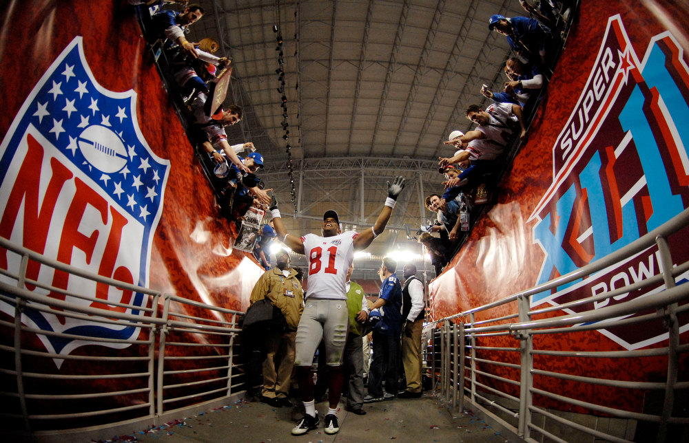 Description of . Amani Toomer #81 of the New York Giants walks off the field after defeating the New England Patriots 17-14 in Super Bowl XLII on February 3, 2008 at the University of Phoenix Stadium in Glendale, Arizona.  (Photo by Michael Heiman/Getty Images)