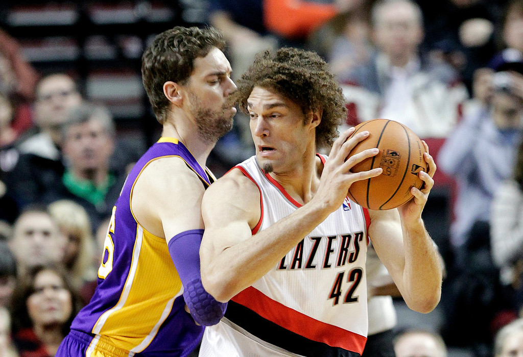 . Portland Trail Blazers center Robin Lopez, right, works the ball in on Los Angeles Lakers center Pau Gasol, of Spain, during the first half of an NBA basketball game in Portland, Ore., Monday, March 3, 2014.(AP Photo/Don Ryan)