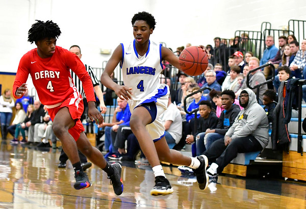 12/29/2018 Mike Orazzi | Staff Bristol Eastern's Jahcyrus Lawrence-Bynum (4) and Derby's Zerion Montgomery (4) during Saturday's boys basketball game in Bristol.