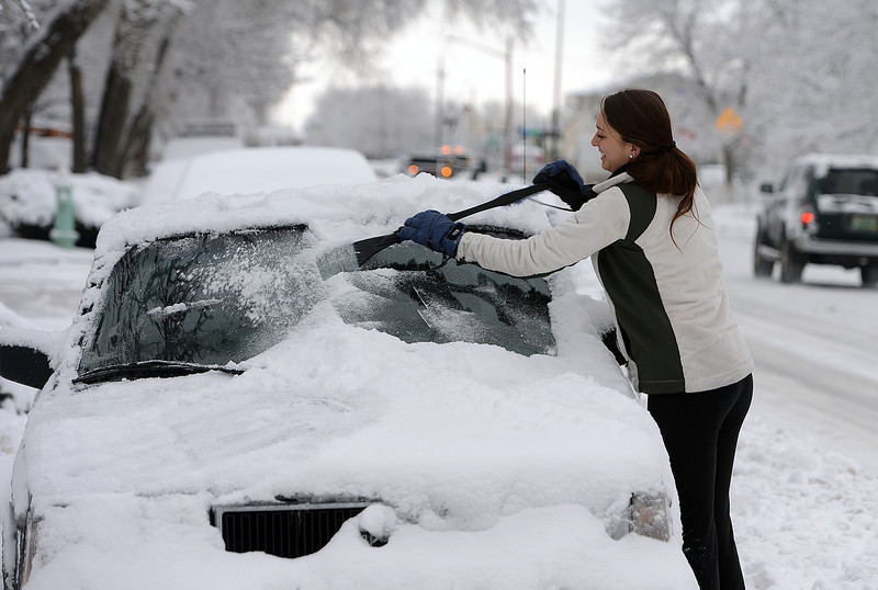 . Jessa Wright scrapes the snow off her car on Spruce Street on Friday, January 31, 2014. (Cliff Grassmick / Daily Camera)