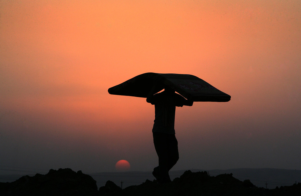 . A Syrian-Kurdish refugee man carries a mattress at sunset at the Quru Gusik refugee camp, 20 kilometres east of Arbil, the capital of the autonomous Kurdish region of northern Iraq, on August 27, 2013. More than 50,000 Syrian refugees have crossed into Iraq\'s Kurdish region in less than two weeks, an official said on August 26, 2013, as authorities rush to house them in more permanent camps.  SAFIN HAMED/AFP/Getty Images