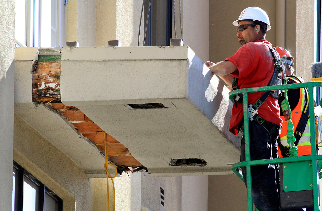 . Workers cut away a strip of outer stucco covering the wood beams that make up the lower balcony to prepare it for removal outside the residential apartment building on Kittredge Street in Berkeley, Calif. on Wednesday, June 17, 2015.  Six people died and seven others were seriously injured when the balcony collapsed early Tuesday morning during a birthday party. (Laura A. Oda/Bay Area News Group)