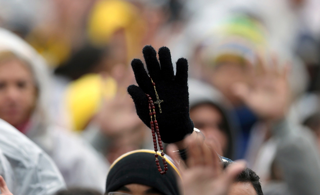 . A person holds up a rosary during Mass celebrated by Pope Francis outside the Aparecida Basilica in Aparecida, Brazil, Wednesday, July 24, 2013. The church is struggling in Latin America to keep Catholics from straying to evangelical and Pentecostal churches that often promise help in finding material wealth, an alluring attraction in a poverty-wracked continent. Francis\' top priority as pope has been to reach out to the world\'s poor and inspire Catholic leaders to go to slums and other peripheries to preach. (AP Photo/Andre Penner)