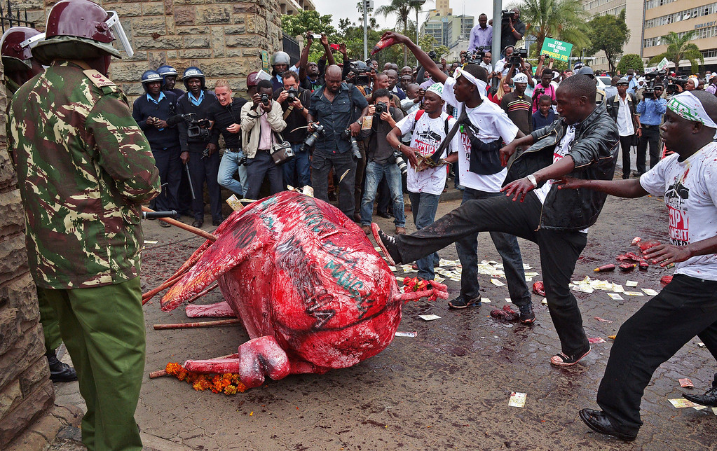 . Protestors kick a sculpture of a pig covered in rotten animal blood towards parliament gates during a demonstration after lawmakers voted themselves hefty salary increases on June 11, 2013 in Nairobi. The protestors had intended to occupy the parliament but were not allowed in by anti-riot police. CARL DE SOUZA/AFP/Getty Images