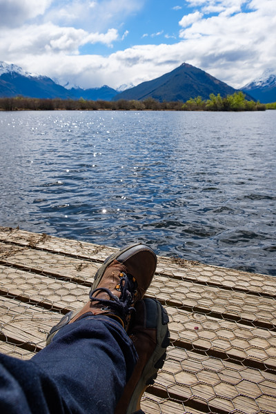 Hiker relaxing at the end of a boardwalk by a lake in South Island, New Zealand