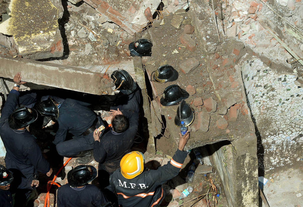 . Firefighters look for survivors at the site of a building collapse in Mumbai on September 27, 2013.  AFP PHOTO/ PUNIT PARANJPE/AFP/Getty Images