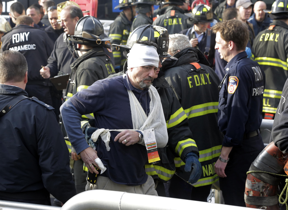 Description of . An injured passenger of the Seastreak Wall Street ferry is aided by New York City firefighters, in New York,  Wednesday, Jan. 9, 2013. The ferry from Atlantic Highlands, N.J., banged into the mooring as it arrived at South Street in lower Manhattan during morning rush hour, injuring as many as 50 people, at least one critically, officials said. (AP Photo/Richard Drew)