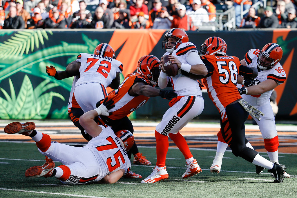 . Cleveland Browns quarterback Cody Kessler, center right, is sacked by Cincinnati Bengals defensive end Chris Smith, center left, and defensive end Carl Lawson (58) in the first half of an NFL football game, Sunday, Nov. 26, 2017, in Cincinnati. (AP Photo/Frank Victores)