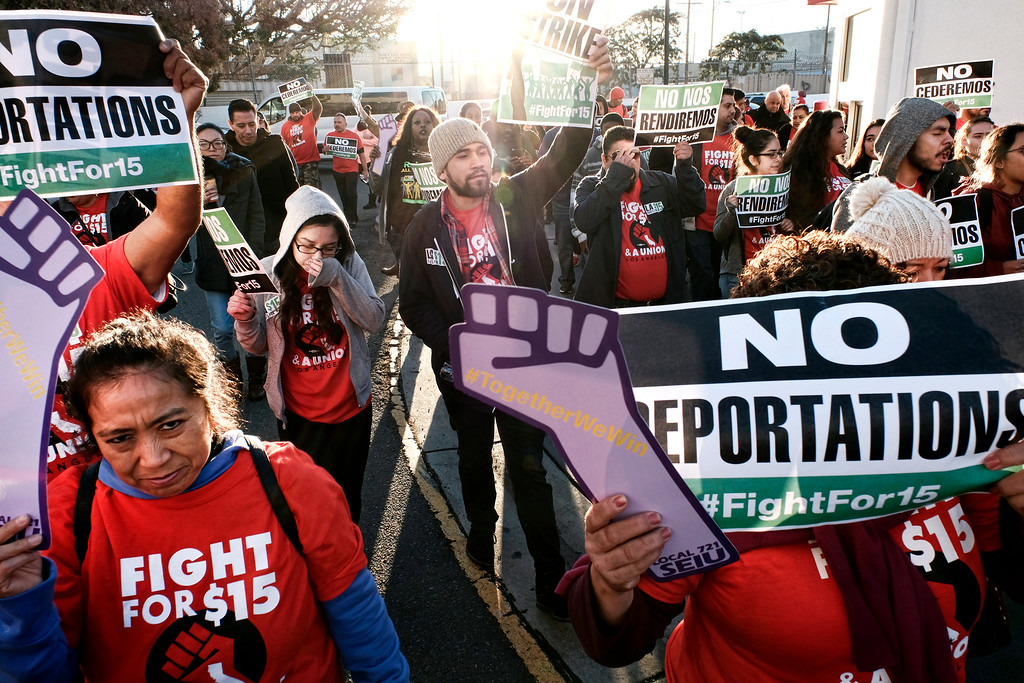 ". Protesters carrying signs and chanting slogans march during a wage protest in downtown Los Angeles on Tuesday, Nov. 29, 2016. Dozens of protesters blocked a downtown Los Angeles intersection as part of a national wave of demonstrations in support of higher wages and workers\' rights. Police stood by as the peaceful demonstrators formed a circle in the street early Tuesday while hoisting signs saying ""the whole world is watching\"" and \""Fight for $15.\"" (AP Photo/Richard Vogel)"