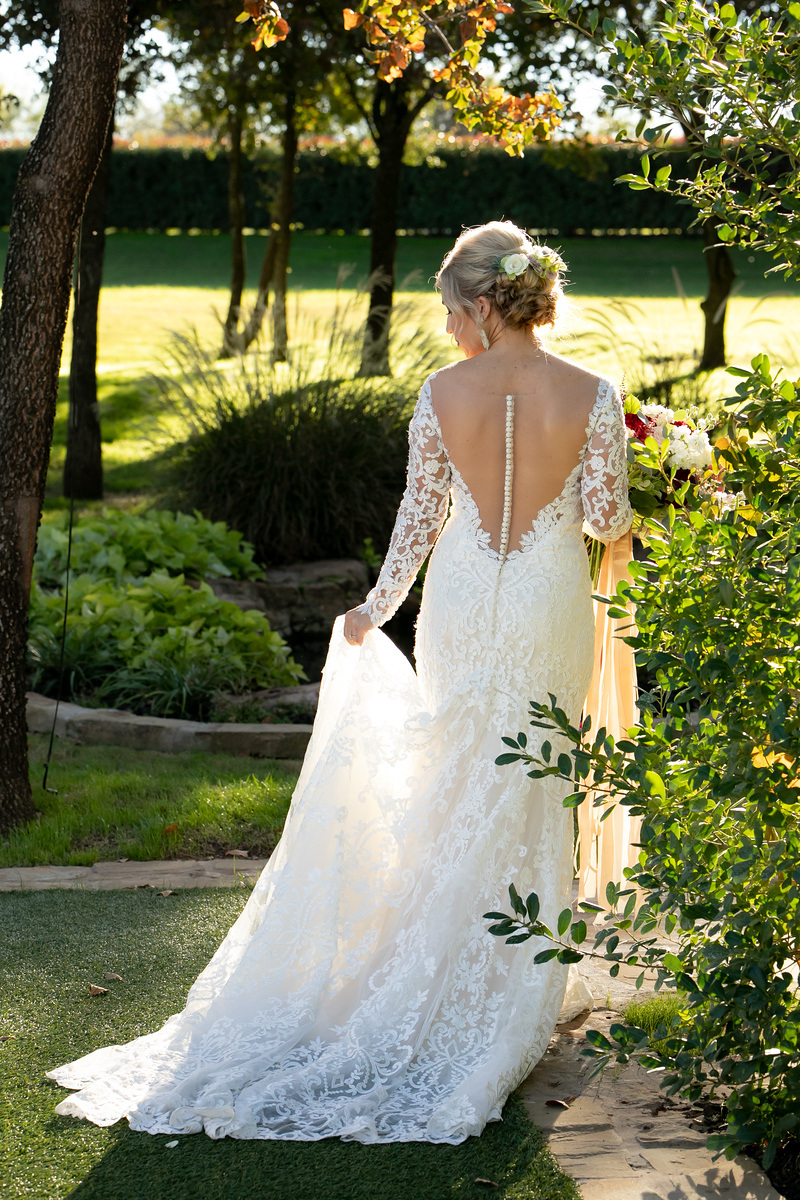 a bride taking a walk through a garden before her wedding ceremony