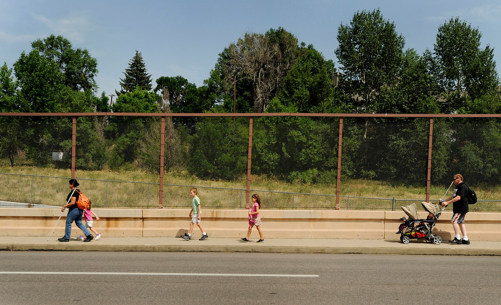 . The Batron family walks down the street to catch the city bus home. Ena and Brent Batron are both blind, and raising their five kids, all under the age of 10.  Photo by Jamie Cotten, Special to The Denver Post