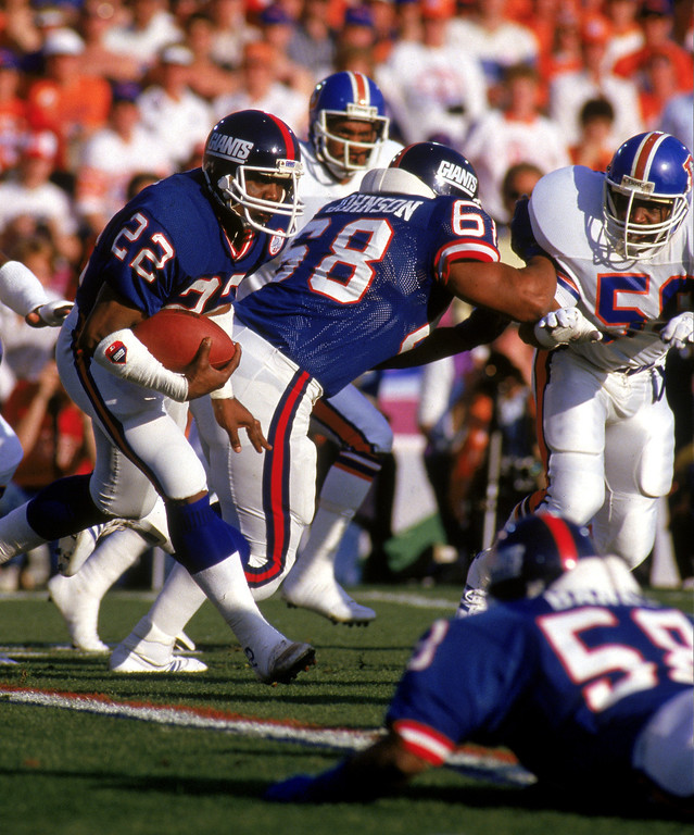 . Running back Lee Rouson #22 of the New York Giants runs with the ball against the Denver Broncos during Super Bowl XXI at the Rose Bowl on January 25, 1987 in Pasadena, California.  (Photo by George Rose/Getty Images)