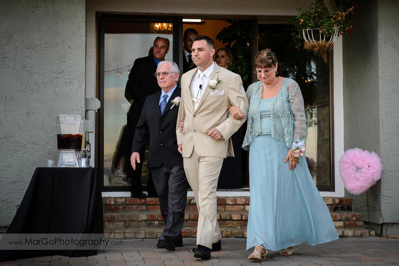 groom walking down to the backyard ceremony side