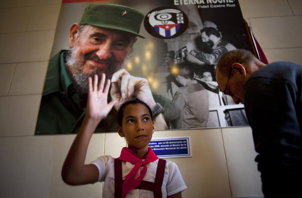Description of . Under a picture of Cuba's leader Fidel Castro, a schoolgirl raises her hand confirming a voter is properly casting his ballot at a polling station during parliament elections in Havana, Cuba, Sunday, Feb. 3, 2013. More than 8 million islanders are eligible to vote and will approve 612 members of the National Assembly and over 1,600 provincial delegates. (AP Photo/Ramon Espinosa)