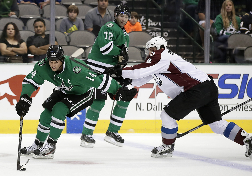 . Dallas Stars left wing Jamie Benn (14) attempts to gain control of the puck under pressure of Colorado Avalanche center Matt Duchene (9) as Stars\' Erik Cole (72) watches in the first period of an NHL hockey game on Thursday, Sept. 26, 2013, in Dallas. (AP Photo/Tony Gutierrez)