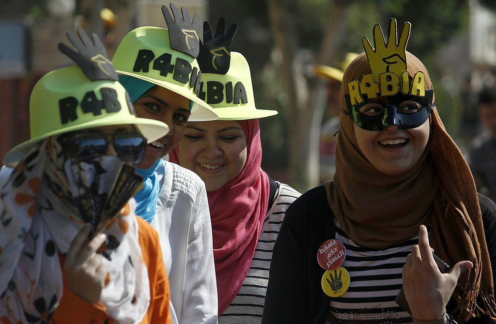 """. Supporters of Egyptian ousted president Mohamed Morsi wear masks and hats with the Rabaa sign as they demonstrate against the military in Cairo\'s eastern Nasr City district on October 11, 2013. Around 2,000 Islamists rallied in Cairo after organisers backtracked from marching on Tahrir Square, avoiding a repeat of last week\'s clashes with police that killed dozens of people. The \""""Rabaa\"""", which means four in Arabic, refers to those killed in the crackdown on the Rabaa al-Adawiya protest camp in Cairo earlier in the year. MOHAMED ABDELMENIEM/AFP/Getty Images"""