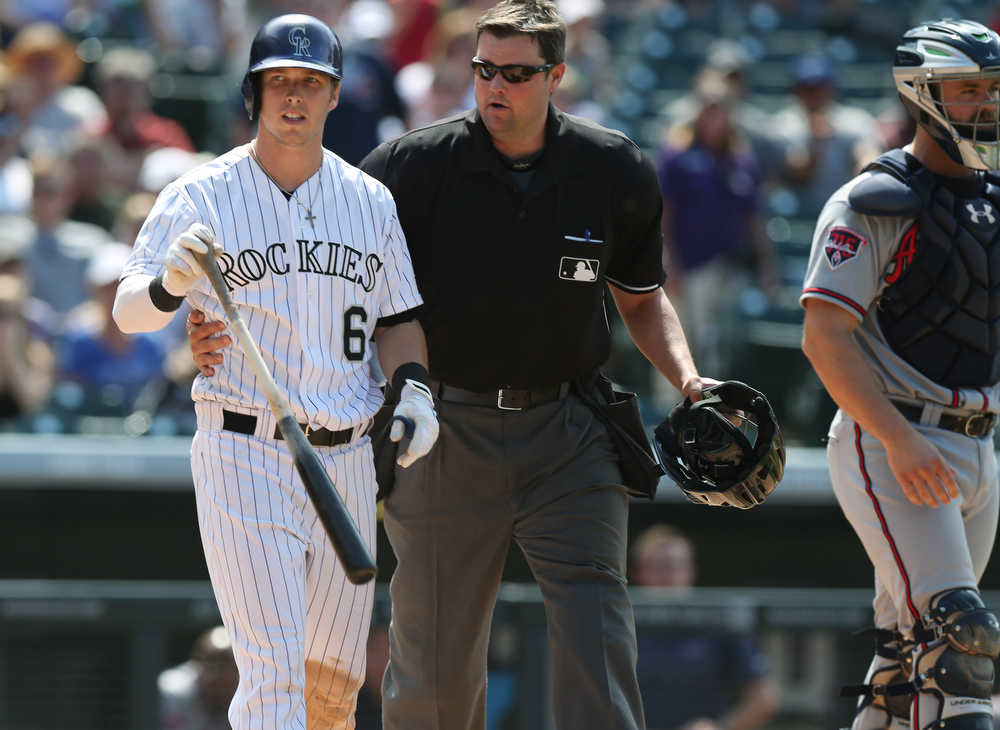. Colorado Rockies\' Corey Dickerson, left, is restrained by home plate umpire Jordan Baker as he walks Dickerson down the first-base line after he was hit by a pitch thrown by Atlanta Braves relief pitcher David Carpenter in the eighth inning of the Rockies\' 10-3 victory in a baseball game in Denver on Thursday, June 12, 2014. Braves catcher Evan Gattis, right, looks on. Rockies manager Walt Weiss was ejected for arguing over Dickerson being hit by the pitch. (AP Photo/David Zalubowski)
