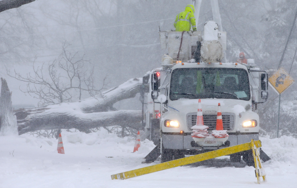 . Workers remove a fallen tree from a road and repair power lines during a winter storm, Tuesday, March 13, 2018, in Norwell, Mass. The nor\'easter is expected to deliver up to 2 feet of snow to some areas of New England. (AP Photo/Steven Senne)