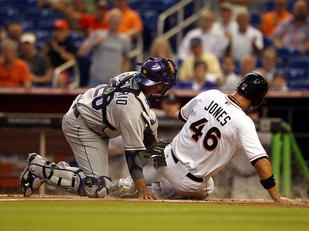 . Catcher Willin Rosario #20 of the Colorado Rockies cannot tag out Garrett Jones #46 of the Miami Marlins during the third inning at the Marlins Park on April 1, 2014 in Miami, Florida.  (Photo by Marc Serota/Getty Images)