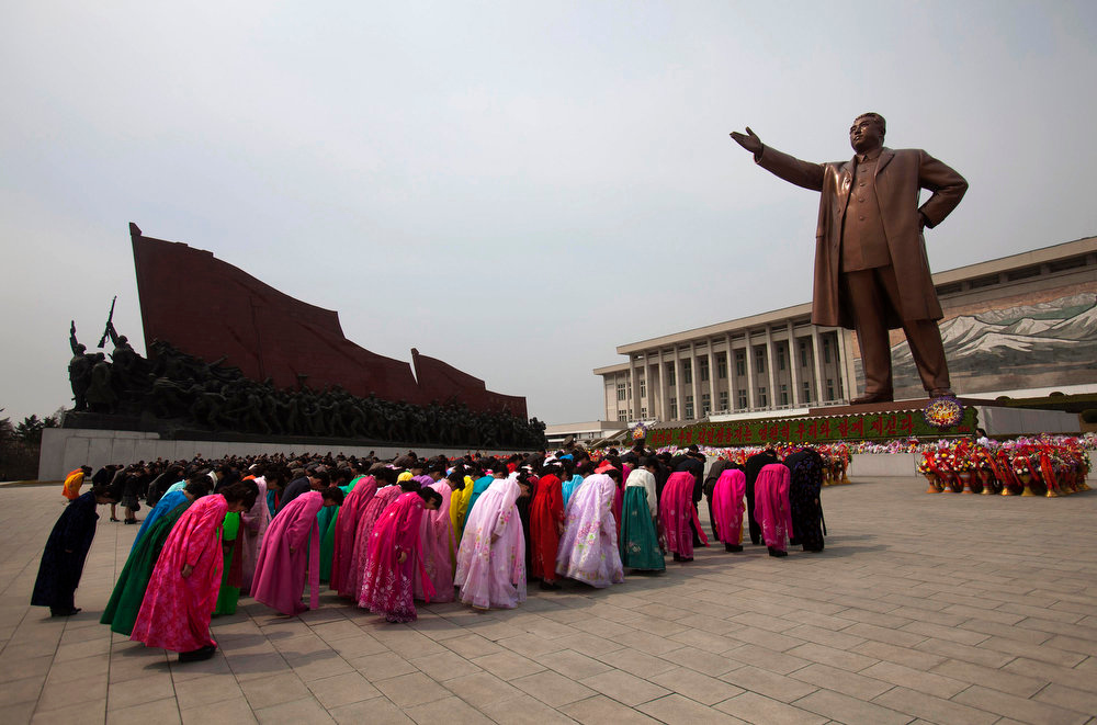 Description of . North Koreans pay their respects before a monument of Kim Il Sung at Mansu Hill in Pyongyang, North Korea on Thursday April 14, 2011. April 15 is called