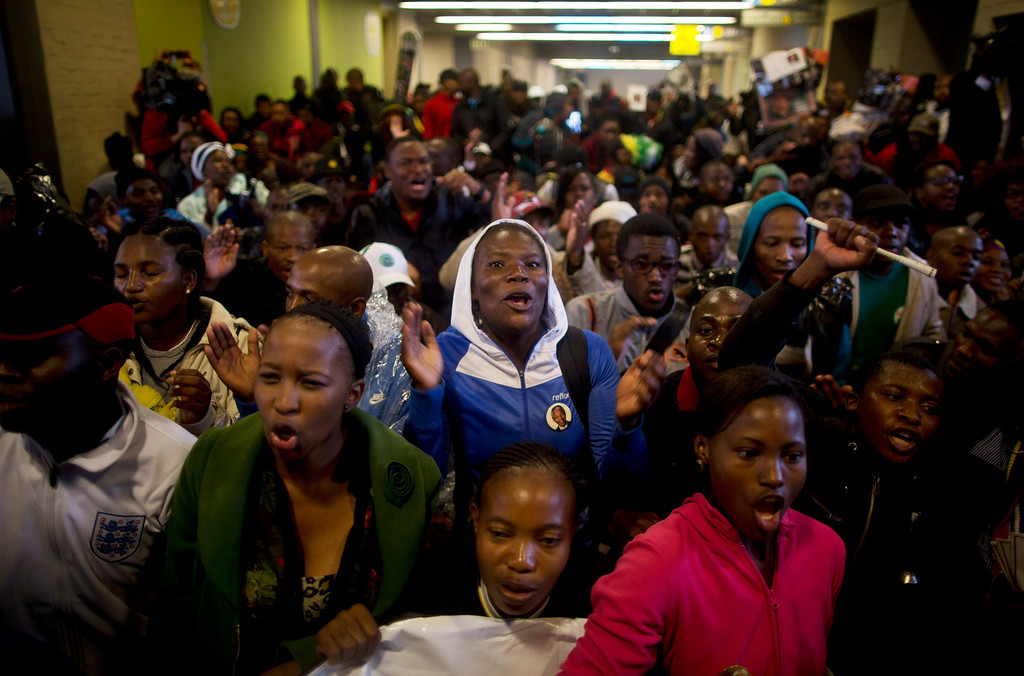 . Mourners sing as they stay out of the rain in the hallways of the FNB Stadium as they wait for the memorial service for former South African president Nelson Mandela in Soweto near Johannesburg, Tuesday, Dec. 10, 2013. (AP Photo/Muhammed Muheisen)