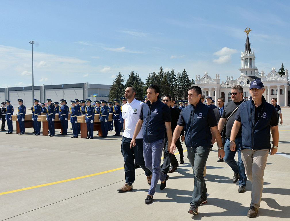. International experts walk to a plane during a ceremony at the airport of Kharkiv, Ukraine, on July 23, 2014, to transport the remains of victims of the Malaysia Airlines flight MH17 crash to the Netherlands. The first plane carrying bodies from downed Malaysia Airlines flight MH17 left eastern Ukraine for the Netherlands on July 23 following a sombre ceremony. The Dutch military aircraft took off from the airport in the government-controlled city of Kharkiv bound for Eindhoven after the first group of victims\' remains were loaded onto the plane in wooden coffins.   AFP PHOTO/ GENYA  SAVILOV/AFP/Getty Images