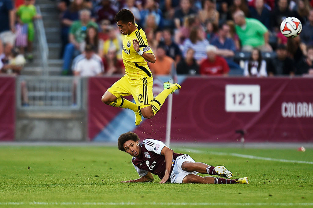 . Chris Klute #15 of the Colorado Rapids slide tackles Hector Jimenez #12 of the Columbus Crew during the first half of an MLS match at Dick\'s Sporting Goods Park on July 4, 2014, in Commerce City, Colorado. The Rapids and Crew finished in a 1-1 draw. (Photo by Daniel Petty/The Denver Post)