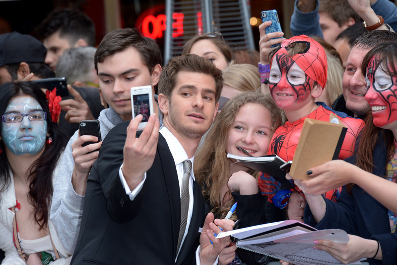 . British actor Andrew Garfield takes a \'selfie\' with fans as he arrives on the red carpet for the world premiere of The Amazing Spider-Man 2 in Leicester Square, London, Thursday April 10, 2014. (Photo by Jon Furniss/Invision/AP)