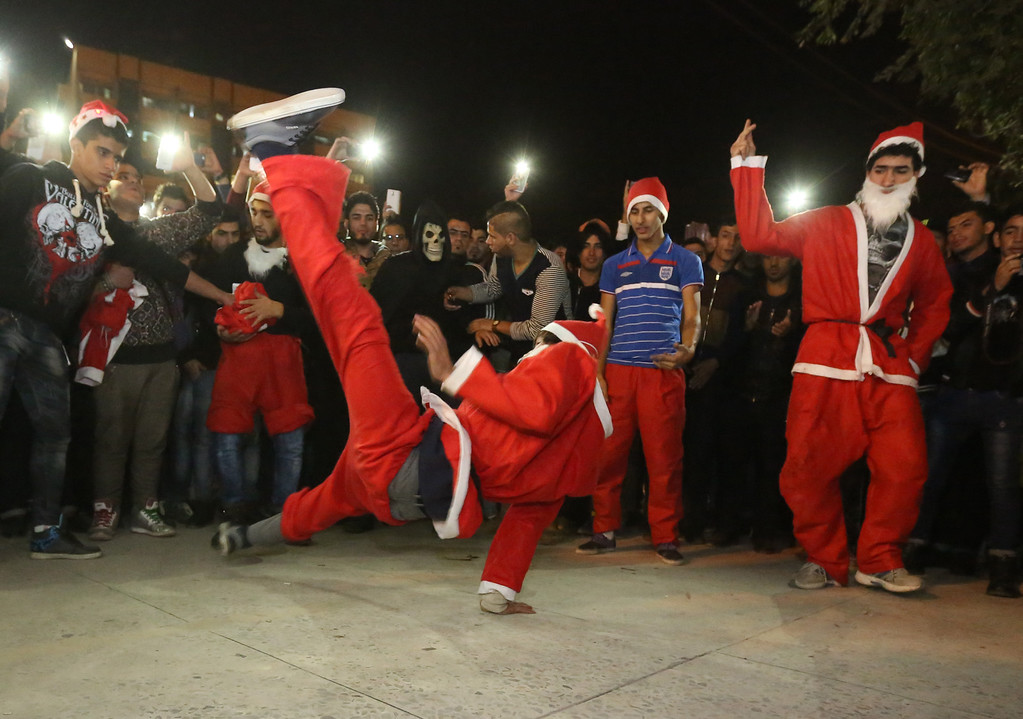 . Acrobatic performers, dressed in Santa Claus costumes, celebrate the New Year at Firdous Square in Baghdad, Iraq, Wednesday, Dec. 31, 2014. (AP Photo/Hadi Mizban)