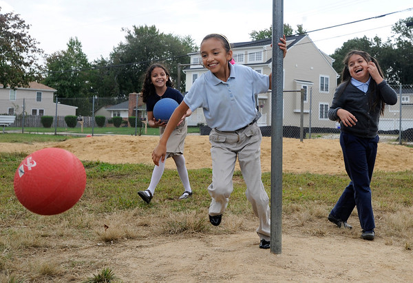 (LtoR) Yoana Velasquez, 8, looks on while Angelica Garcia, 8 chases the ball and Ruth Cruz, 8 laughs during recess at Mills-Parole Elementary School. (Photo by Shannon Lee Zirkle - The Capital)