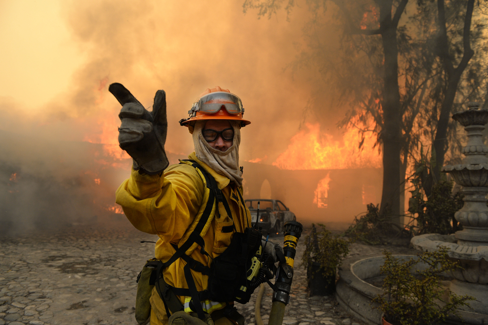 . A fireman calls for more water on the burning Singer home above Glendora, Calif., Thursday Jan. 16, 2014.  The wildfire in the foothills of Southern California\'s San Gabriel Mountains, burned a portion of the former Singer home, of sewing machine fame.  (AP Photo/The Inland Valley Daily Bulletin,Will Lester)