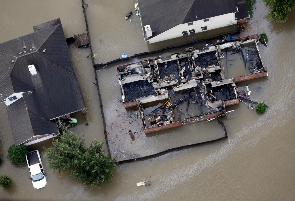 . A burned out home is surrounded by floodwaters from Tropical Storm Harvey Tuesday, Aug. 29, 2017, in Spring, Texas. (AP Photo/David J. Phillip)