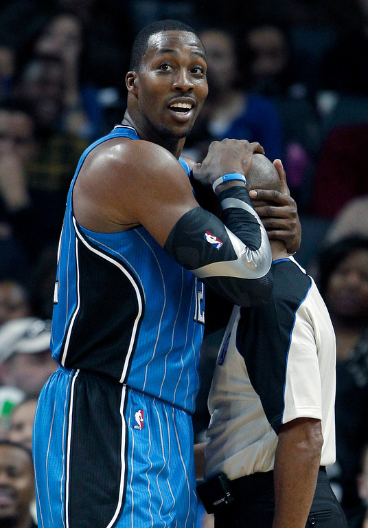 . Orlando Magic\'s Dwight Howard, left, embraces referee Derrick Stafford, right, after Stafford\'s call on Howard during the second half of an NBA basketball game against the Charlotte Bobcats in Charlotte, N.C., Friday, Dec. 30, 2011. The Magic won 100-79. (AP Photo/Chuck Burton)