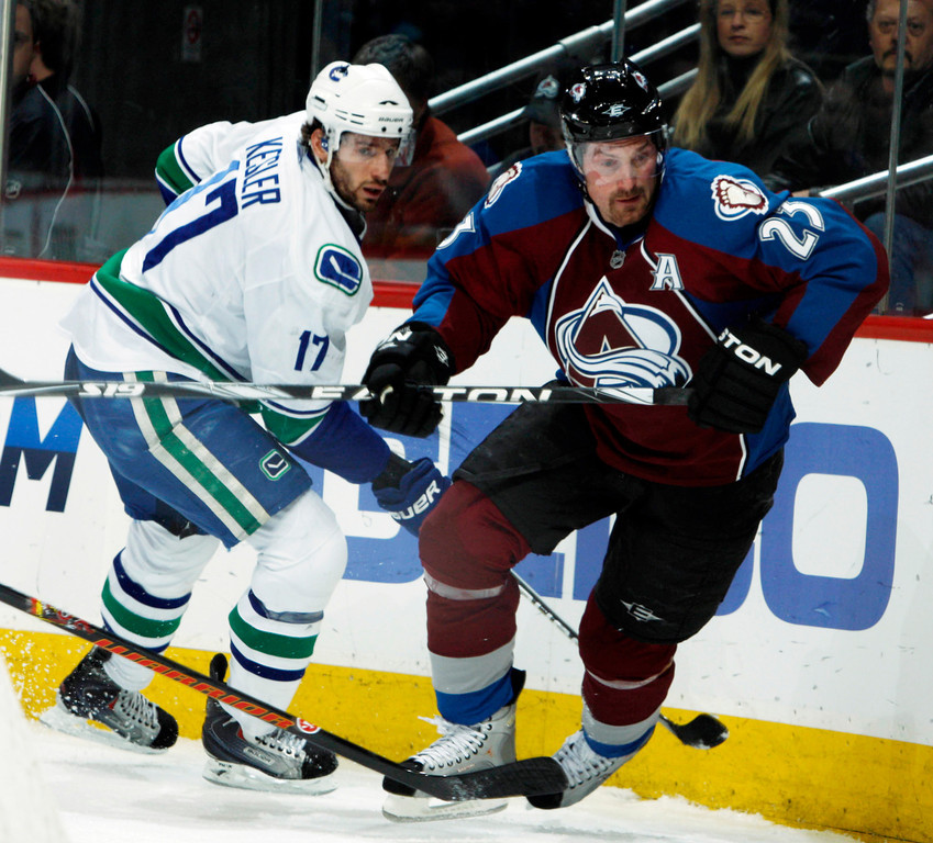 . Vancouver Canucks center Ryan Kelser, left, and Colorado Avalanche right winger Milan Hejduk, of the Czech Republic, pursue a loose puck in the first period of an NHL hockey game in Denver on Tuesday, March 9, 2010. (AP Photo/David Zalubowski)