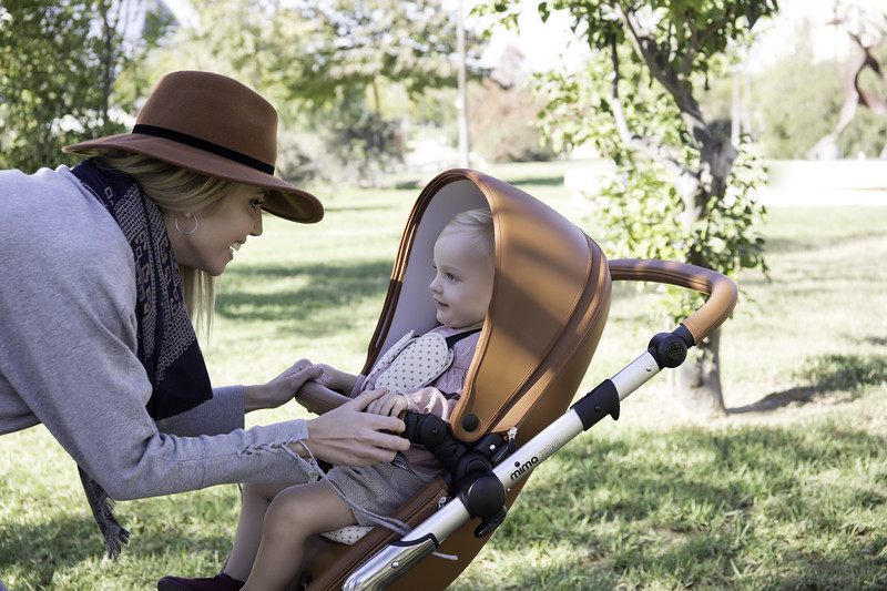 Mima_Xari_Lifestyle_Camel_Aluminium_Chassis_Mum_Playing_With_Baby_In_Pushchair_Side_Angle.jpg