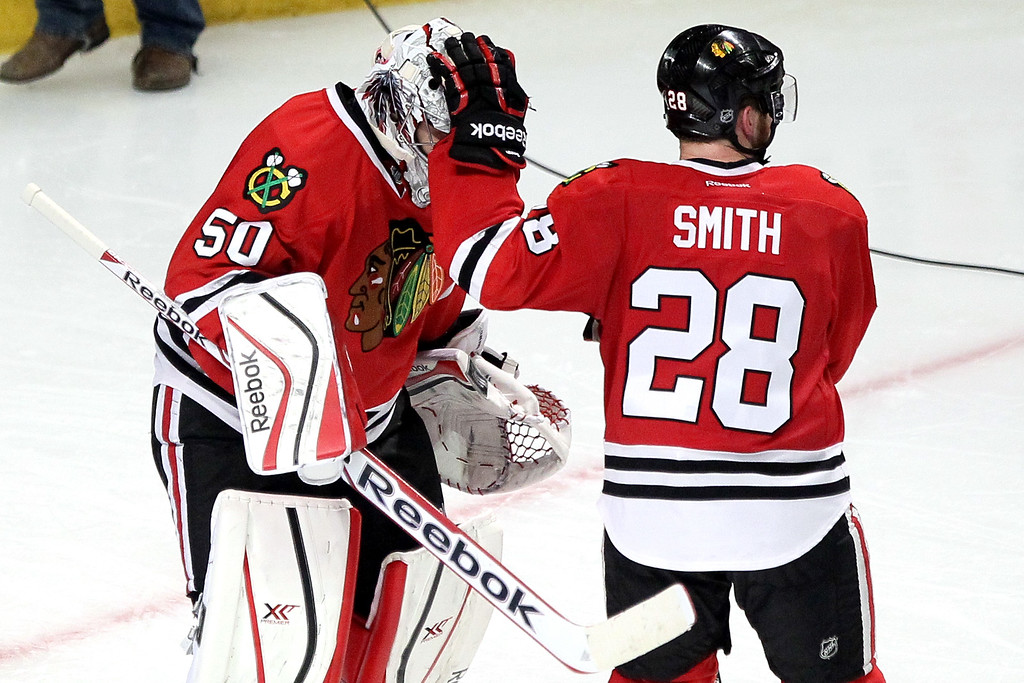 . Corey Crawford #50 and Ben Smith #28 of the Chicago Blackhawks celebrate after defeating the Los Angeles Kings in double overtime of Game Five of the Western Conference Final in the 2014 Stanley Cup Playoffs at United Center on May 28, 2014 in Chicago, Illinois.  The Chicago Blackhawks defeated the Los Angeles Kings 5 to 4.  (Photo by Tasos Katopodis/Getty Images)